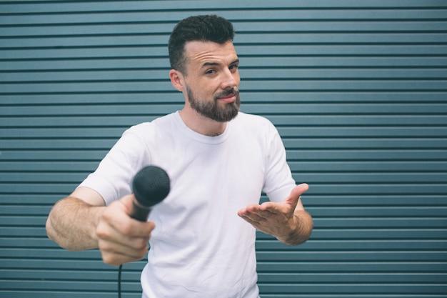 Le chanteur positif tient le microphone dans les mains. lui et pointant dessus. guy propose de chanter. l'homme sourit. isolé sur rayé