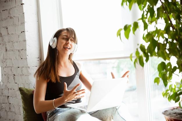 Chanteuse caucasienne lors d'un concert en ligne à la maison isolée et mise en quarantaine,