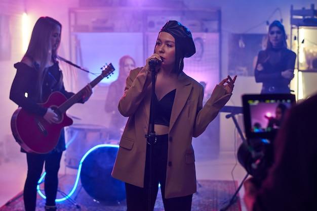 Chanteuse chantant au micro et jouant avec son groupe et enregistrant leur concert sur la vidéo