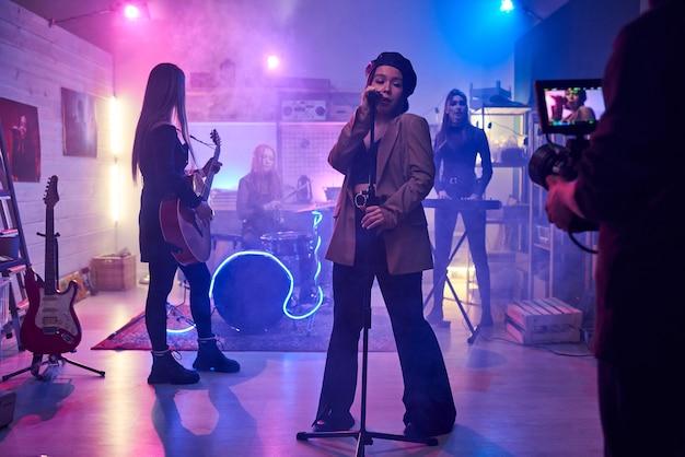 Chanteuse chantant au micro et jouant avec son groupe de musique dans la boîte de nuit