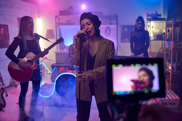 La chanteuse chante au micro pendant que son groupe joue sur des instruments de musique, ils tournent un clip