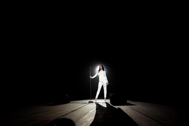 Chanteuse femme sur scène avec fond noir dans un faisceau de lumière blanche.