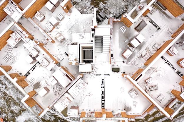 Chantier de construction abandonné enneigé, vue de dessus, tir de drone.