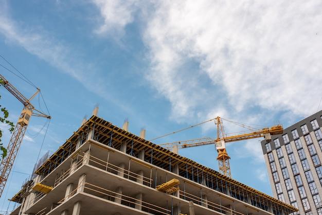 Chantier de construction de grues et de bâtiments contre le ciel bleu