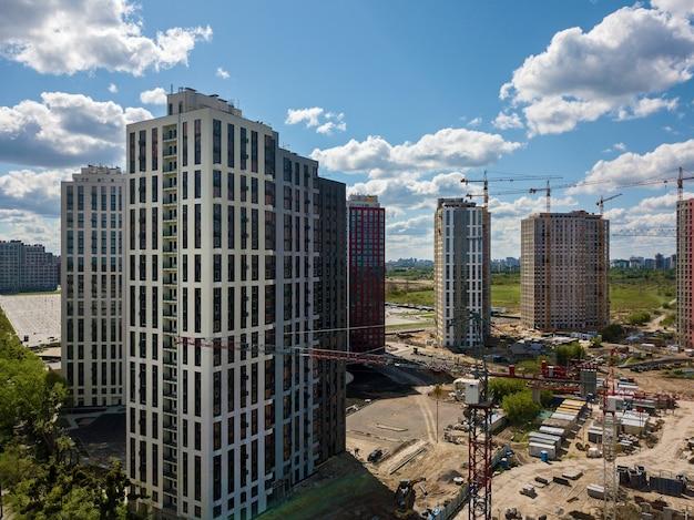 Chantier de construction avec grues à tour de bâtiments à plusieurs étages et construction de matériel de construction