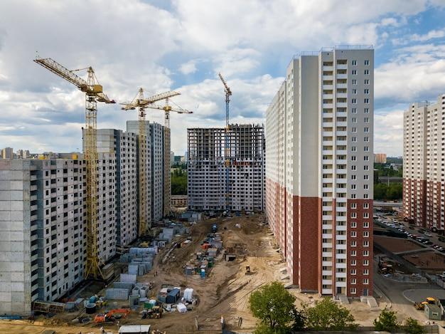 Chantier de construction avec des grues à tour de bâtiments à plusieurs étages et des équipements de construction