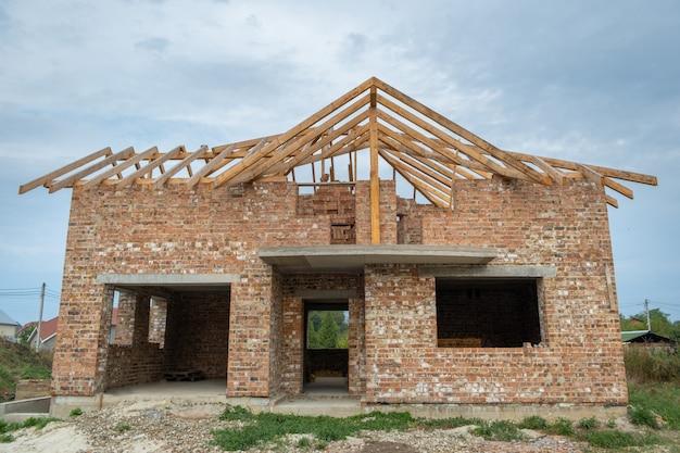 Chantier de construction avec maison en briques inachevée avec charpente en bois pour futur toit en construction.