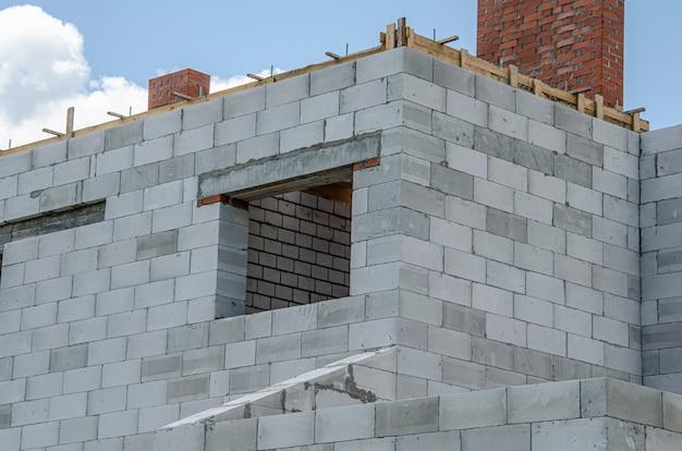 Chantier de construction d'une maison en construction faite de blocs de béton mousse blancs. construction d'un nouveau cadre de maison.