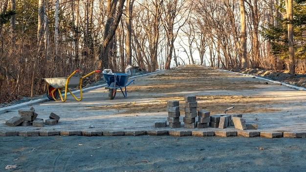 Chantier de construction et pavage sur un sentier pédestre dans un parc public. scène de travaux préparatoires avec des chariots pour le transport du sol. carrelage en cours de pose