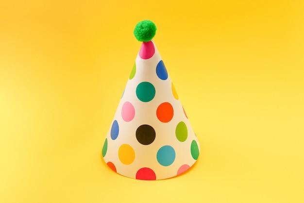 Chapeau d'anniversaire coloré sur fond jaune