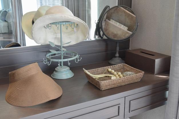 Chapeau blanc et bijoux posés sur une commode dans une pièce contemporaine.