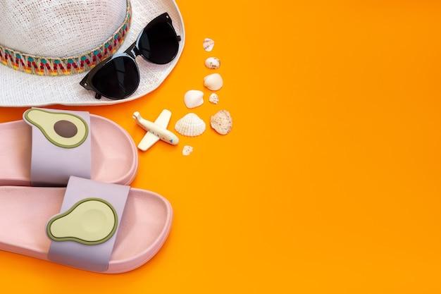 Chapeau blanc paille femme élégante lunettes de soleil noires tongs de plage violettes roses avec avion jouet moitiés avocat et coquillages isolés sur un mur orange de couleur vive