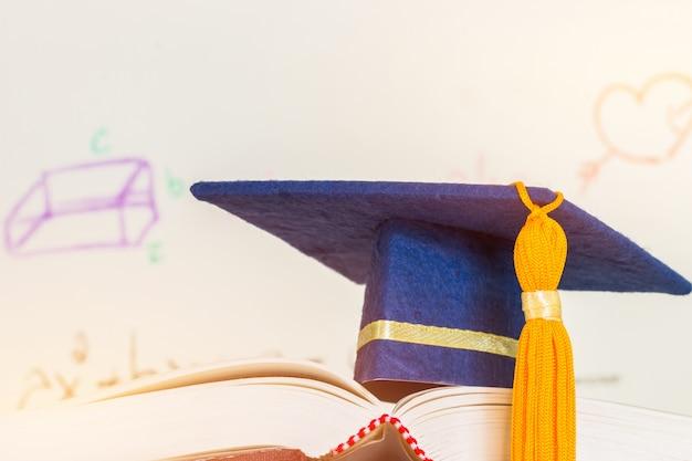 Chapeau bleu de mortier diplômé de l'éducation sur les manuels scolaires avec équation de formule ou de mathématiques à l'écran
