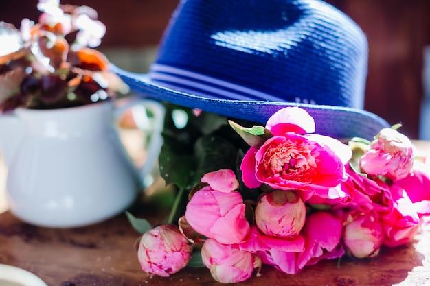 Chapeau bleu se trouve sur un bouquet de pivoines roses