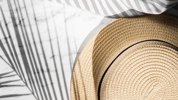 Chapeau brun pâle et un drap rayé gris et blanc sur un fond blanc recouvert d'une ombre de feuille