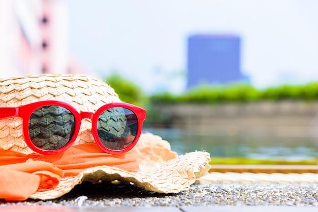 Chapeau brun à la piscine et lunettes de soleil rouges en soirée avec l'heure du coucher du soleil.