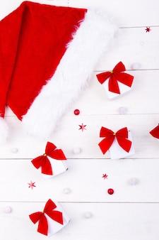 Chapeau et cadeaux de noël, petites boîtes blanches avec un arc rouge et des bonbons