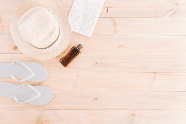 Chapeau; carte; tongs et bouteille sur fond de planche de bois