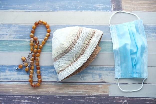 Chapeau de chapelet de prière et masque sur table