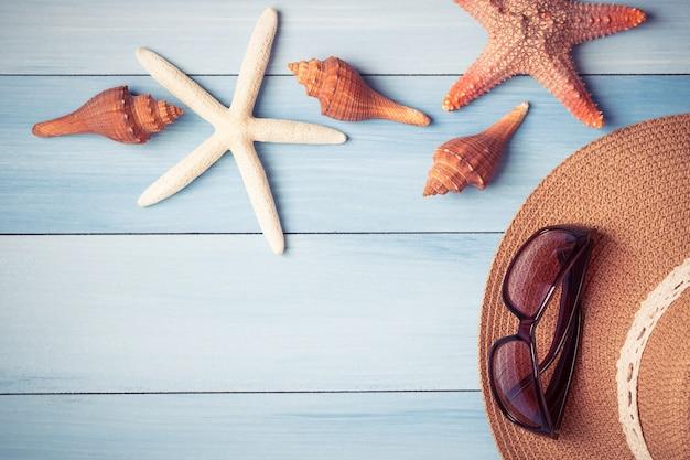 Chapeau et coquillages sur le plancher en bois du bleu, concept d'été