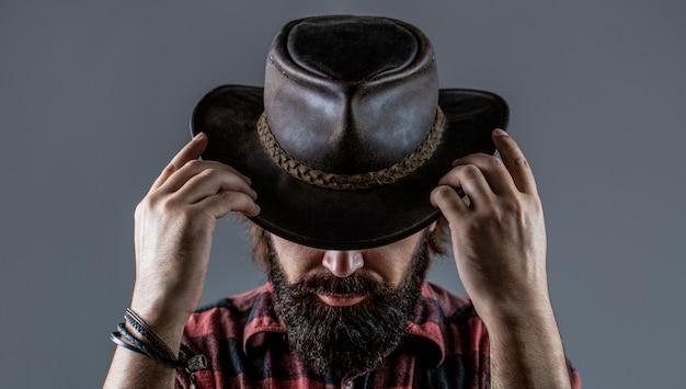 Chapeau de cowboy en cuir. portrait de jeune homme portant un chapeau de cowboy. cowboys au chapeau. beau macho barbu. homme cowboys mal rasés. cowboy américain.