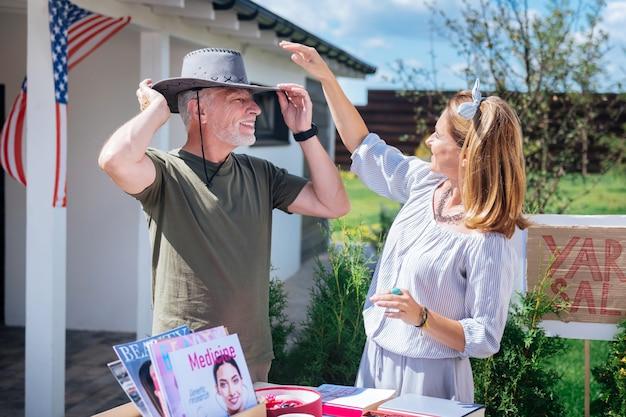 Chapeau de cowboy. homme gai rayonnant d'essayer un chapeau de cow-boy noir tout en assistant à une vente de garage avec sa belle femme élégante