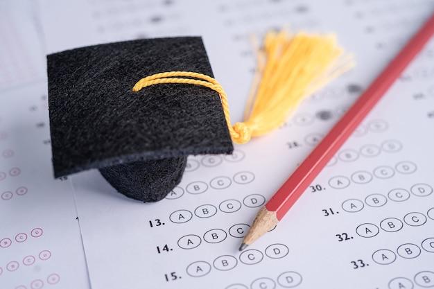 Chapeau et crayon d'écart d'obtention du diplôme sur l'étude de l'éducation d'arrière-plan de feuille de réponses