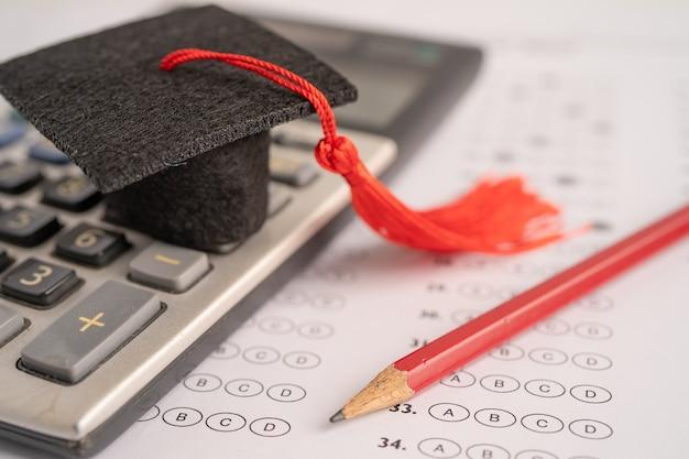 Chapeau et crayon d'écart de remise des diplômes sur l'arrière-plan de la feuille de réponses