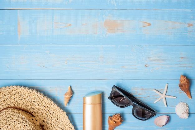 Chapeau, crème solaire, lunettes de soleil et coquille sur bleu