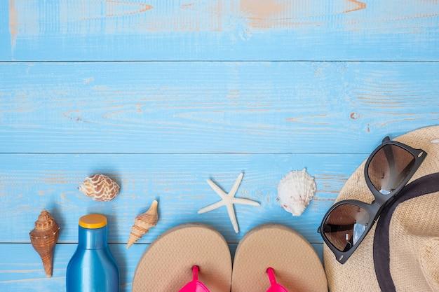 Chapeau, crème solaire, lunettes de soleil, pantoufles et coquille sur bleu