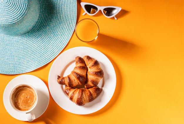 Chapeau, croissant de lunettes de soleil avec une tasse de café et un verre de jus d'orange sur une table jaune au soleil