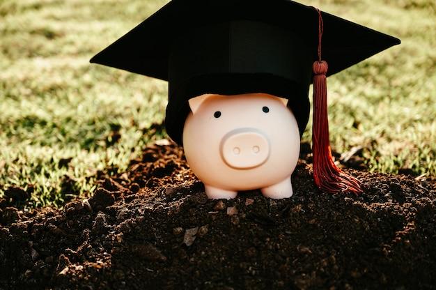 Un chapeau de diplômé noir, des glands marron et une tirelire rose reposaient sur le sol noir.