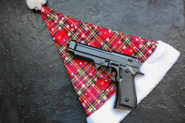 Le chapeau du père noël est allongé sur la table avec une arme à feu. criminel en 2020 nouvel an.