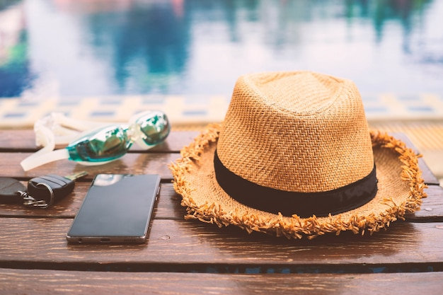 Le chapeau est placé à côté de la table en bois près de la piscine avec un smartphone et des lunettes. style vintage