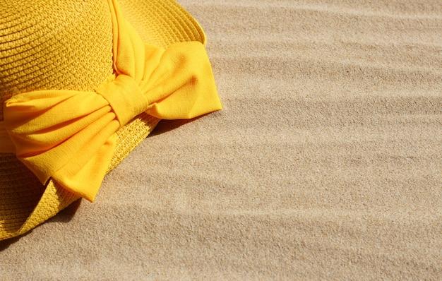 Chapeau d'été jaune avec sur le sable