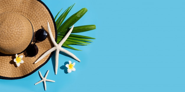 Chapeau d'été avec des lunettes de soleil sur fond bleu. profitez du concept de vacances. copier l'espace