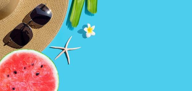 Chapeau d'été avec des lunettes de soleil et des pastèques, des étoiles de mer et des fleurs de frangipanier sur une surface bleue