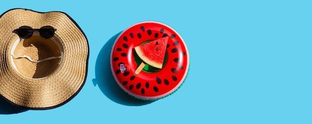 Chapeau d'été et lunettes de soleil avec tranche de pastèque popsicle sur jouet anneau de bain sur fond bleu. concept de fond d'été