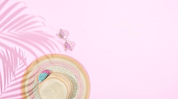 Chapeau d'été rond avec accessoires sur fond rose, avec ombre à la feuille de palmier