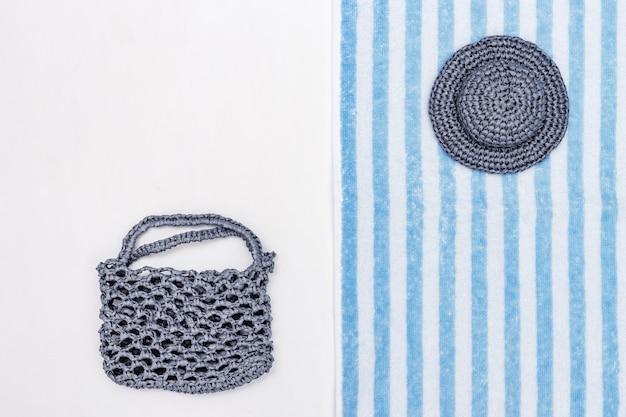 Chapeau d'été, sac de plage, serviette éponge sur fond blanc. fond d'été. style minimal.