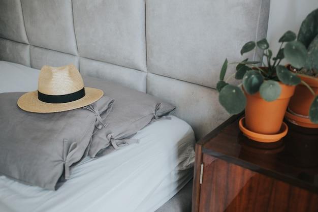 Chapeau fedora mignon sur un lit confortable avec des oreillers