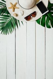 Chapeau femme et accessoires de voyage sur fond en bois blanc avec espace vide