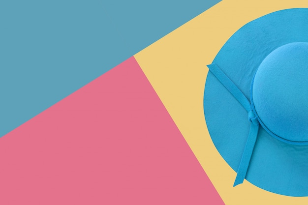 Chapeau de femme d'été bleu sur fond coloré, plat photo laïque