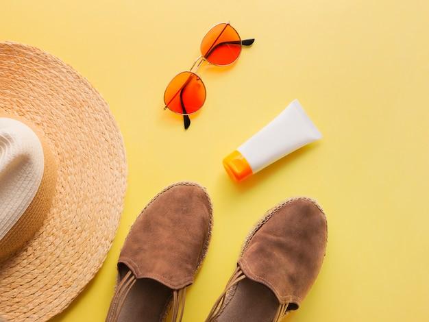 Chapeau de femme en paille avec lunettes de soleil, crème de protection et sandales vue de dessus fond jaune vif à plat.