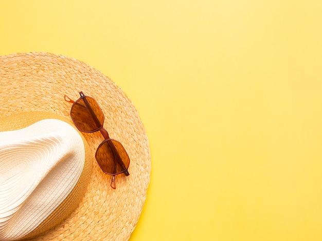 Chapeau de femme de paille avec des lunettes de soleil vue de dessus fond jaune vif plat poser unique