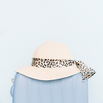 Chapeau de femme sur un sac de voyage en plastique sur fond bleu