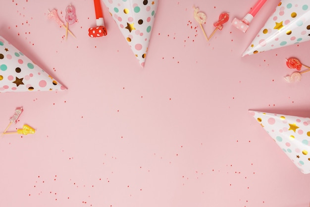 Chapeau de fête et bougies sur fond rose