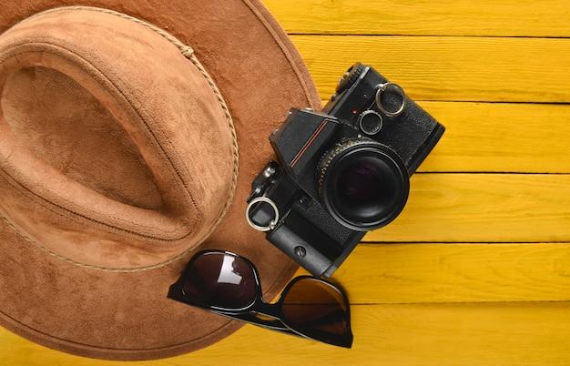 Chapeau en feutre, appareil photo argentique, disposition des lunettes de soleil sur une table en bois colorée. passion pour les voyages, concept wanderlust. mise à plat.