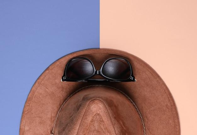 Chapeau en feutre avec lunettes de soleil sur fond coloré. accessoires saisonniers à la mode