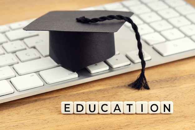Chapeau de graduation sur clavier d'ordinateur sur un bureau en bois